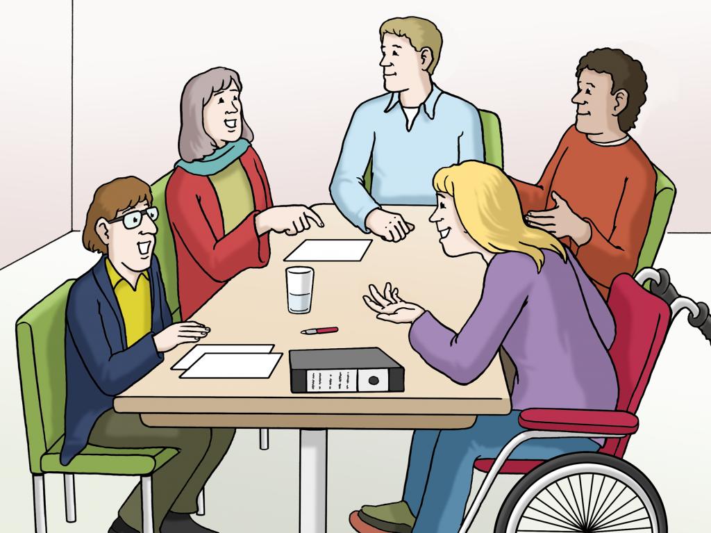 Arbeitssituation: Eine diverse Gruppe von 5 Personen sitzt zusammen am Tisch und diskutiert angeregt.