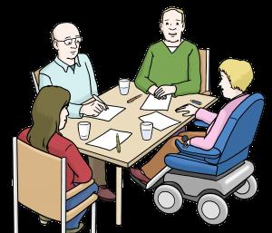 Arbeitsgruppe: Vier Personen, eine davon im Rollstuhl sitzen gemeinsam mit Stiftung und Papier an einem Tisch