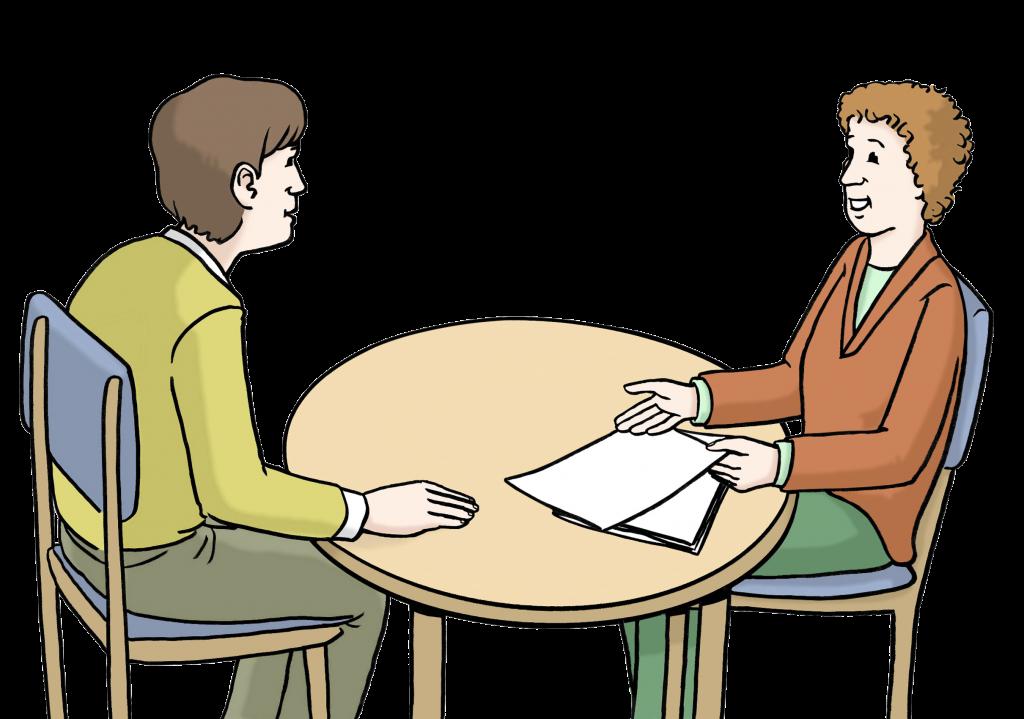 Zwei Personen sitzen an einem runden Tisch. Die eine Person berät die andere