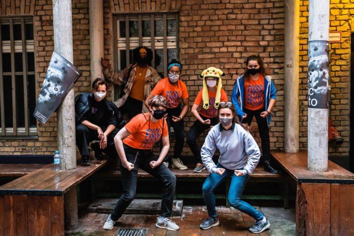 """Eine Gruppe von 7 Projektteilnehmenden und Projektleitenden steht vor einem Gebäude aus Backstein. 5 der Personen spannen ihre Armmuskeln an, ähnlich wie bei einer Bodybuilder-Show. 4 Personen tragen ein Projekt-T-Shirt mit der Aufschrift """"Error Music""""."""