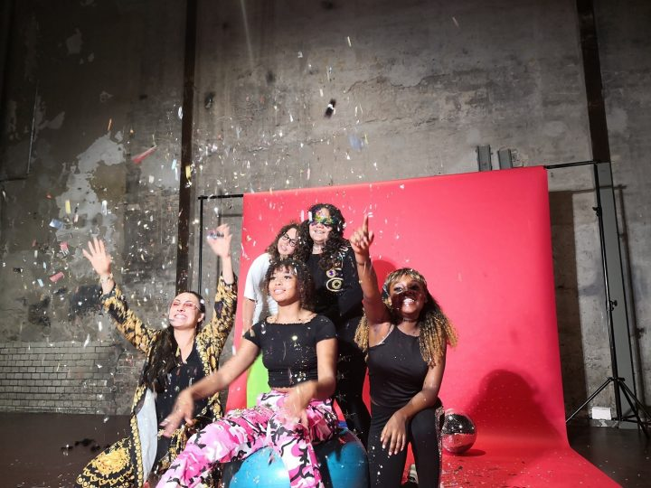 Fünf Mädchen und Frauen positionieren sich lachend zum Gruppenfoto. Dabei fliegt Konfetti. Im Hintergrund ist eine Leinwand und eine auf dem Boden liegende Diskokugel. Ein Mädchen sitzt auf einem Gymnastikball, neben ihr hockt links und rechts jeweils eine weitere Person. Zwei Projektteilnehmerinnen stehen mit aneinander gelehnten Köpfen dahinter.
